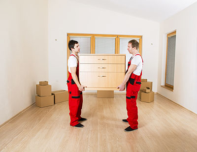 two men standing with chest of drawers