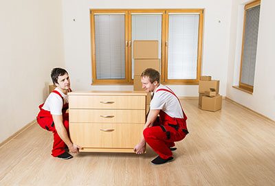 many hand makes light work, image of two men lifting a chest of drawers