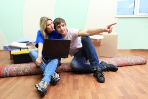 Couple sat on a rug planning a home move