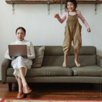 Image of woman trying to work with daughter jumping on the sofa next to her